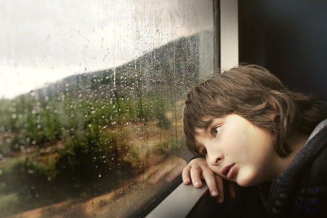 Junge vor Fenster im Regen